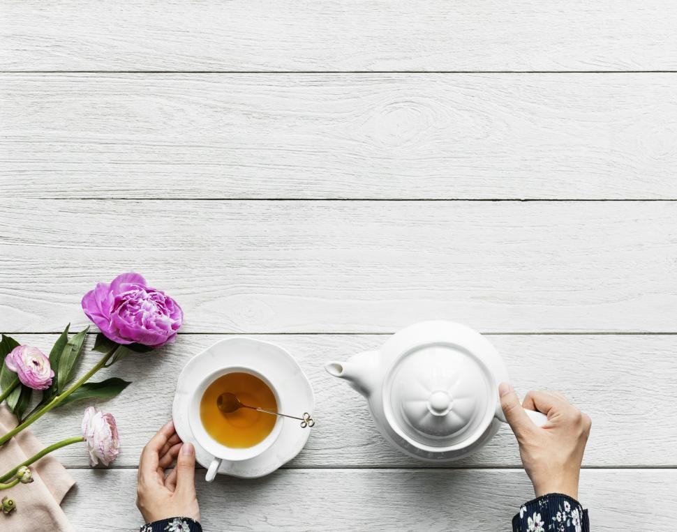 Download Free Stock Photo of Overhead view of a cup of tea alongside a kettle and purple flower