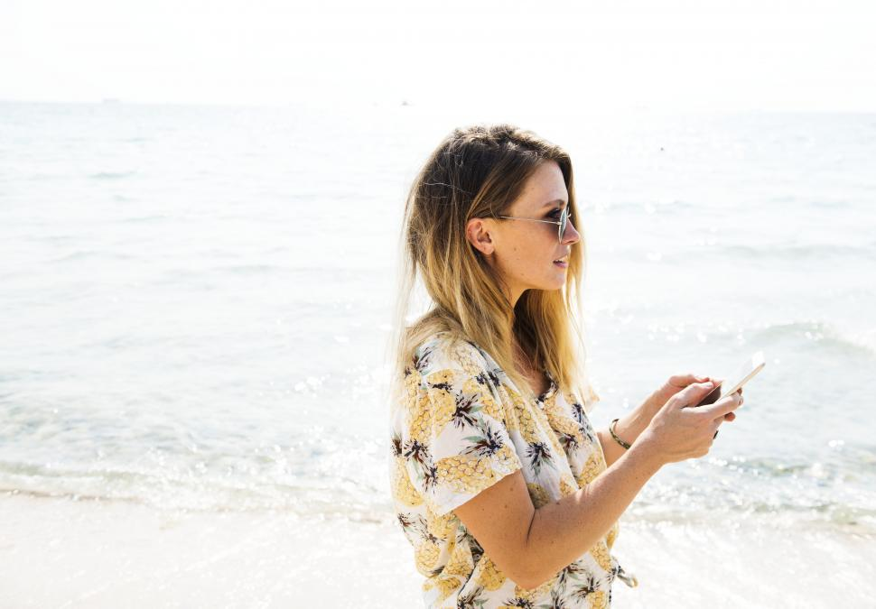 Download Free Stock HD Photo of A young woman on the beach with a smartphone Online