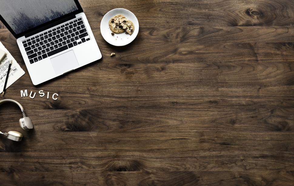 Download Free Stock Photo of Overhead view of a laptop on dark wood table and an audio headset