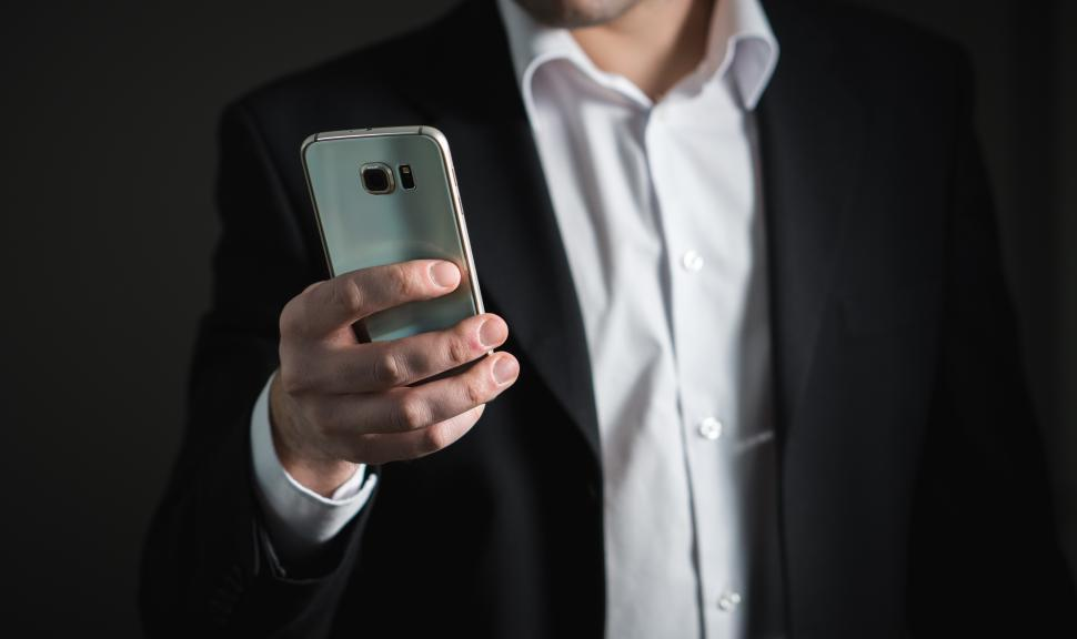 Download Free Stock HD Photo of Close up of a business person viewing his mobile phone Online