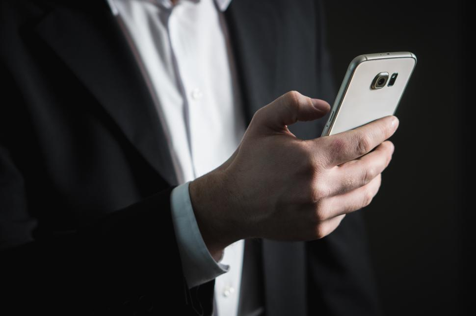 Download Free Stock Photo of Close up of a business person looking at mobile phone