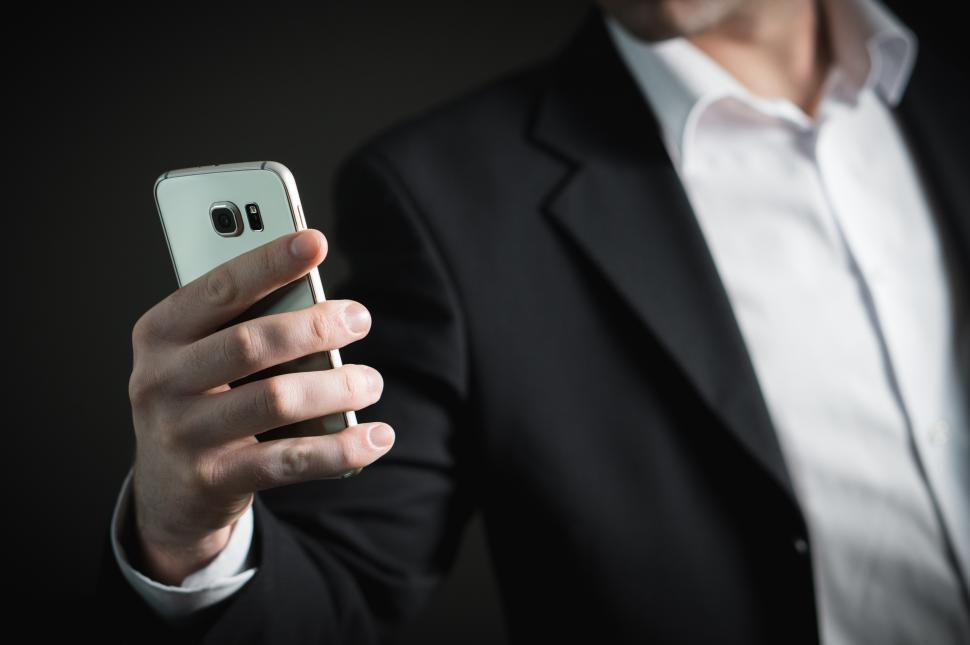 Download Free Stock HD Photo of Close up of a business person looking at mobile phone Online