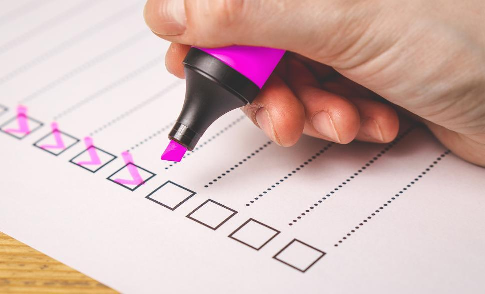 Download Free Stock Photo of Side view of a hand writing on a checklist with magenta marker