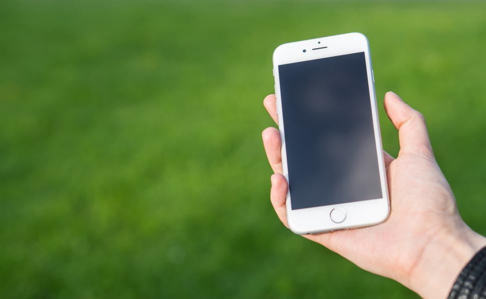 Download Free Stock HD Photo of A hand posing with a smartphone over green grass Online