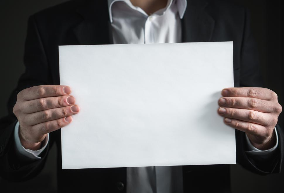 Download Free Stock HD Photo of A business person holding a blank sheet of paper Online