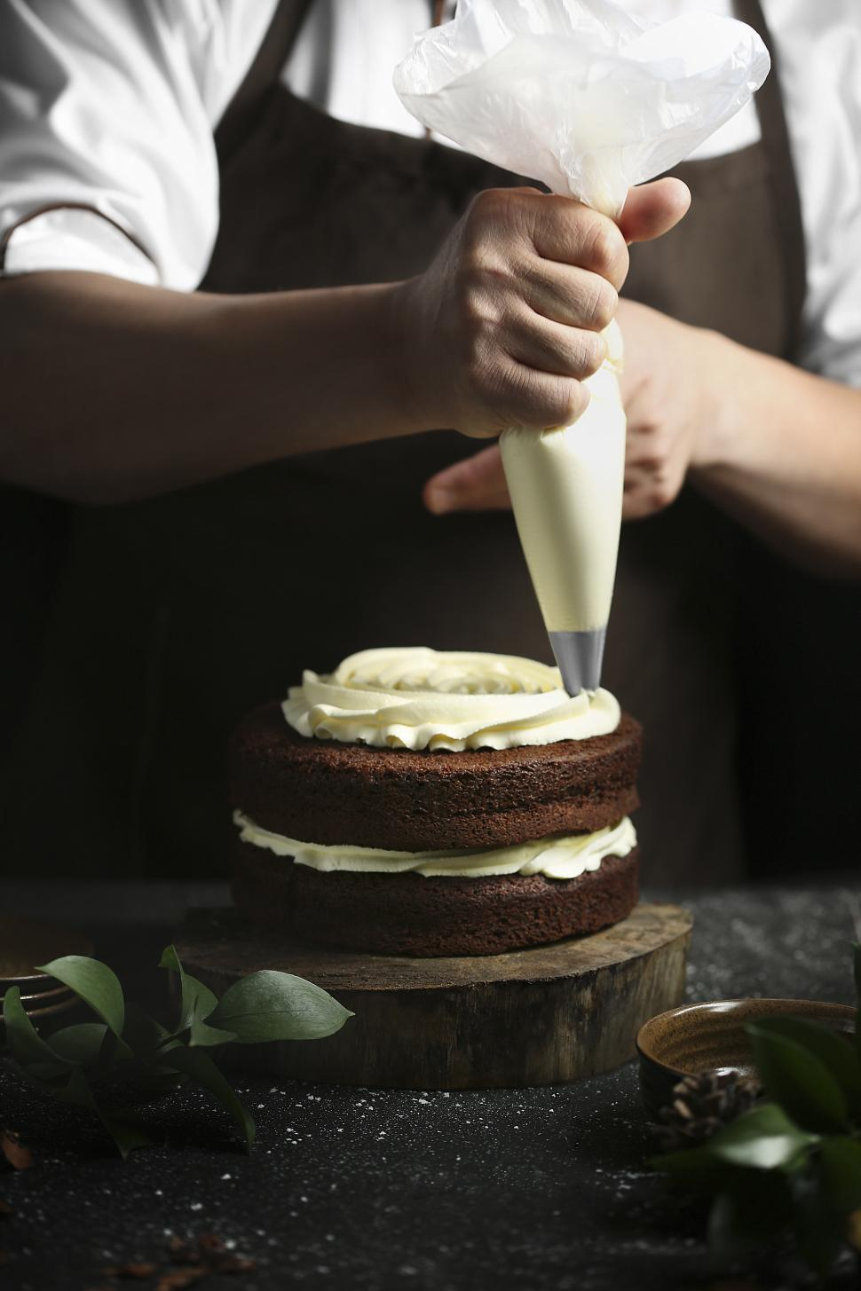 Download Free Stock HD Photo of Piping white cream onto chocolate cake with piping bag Online