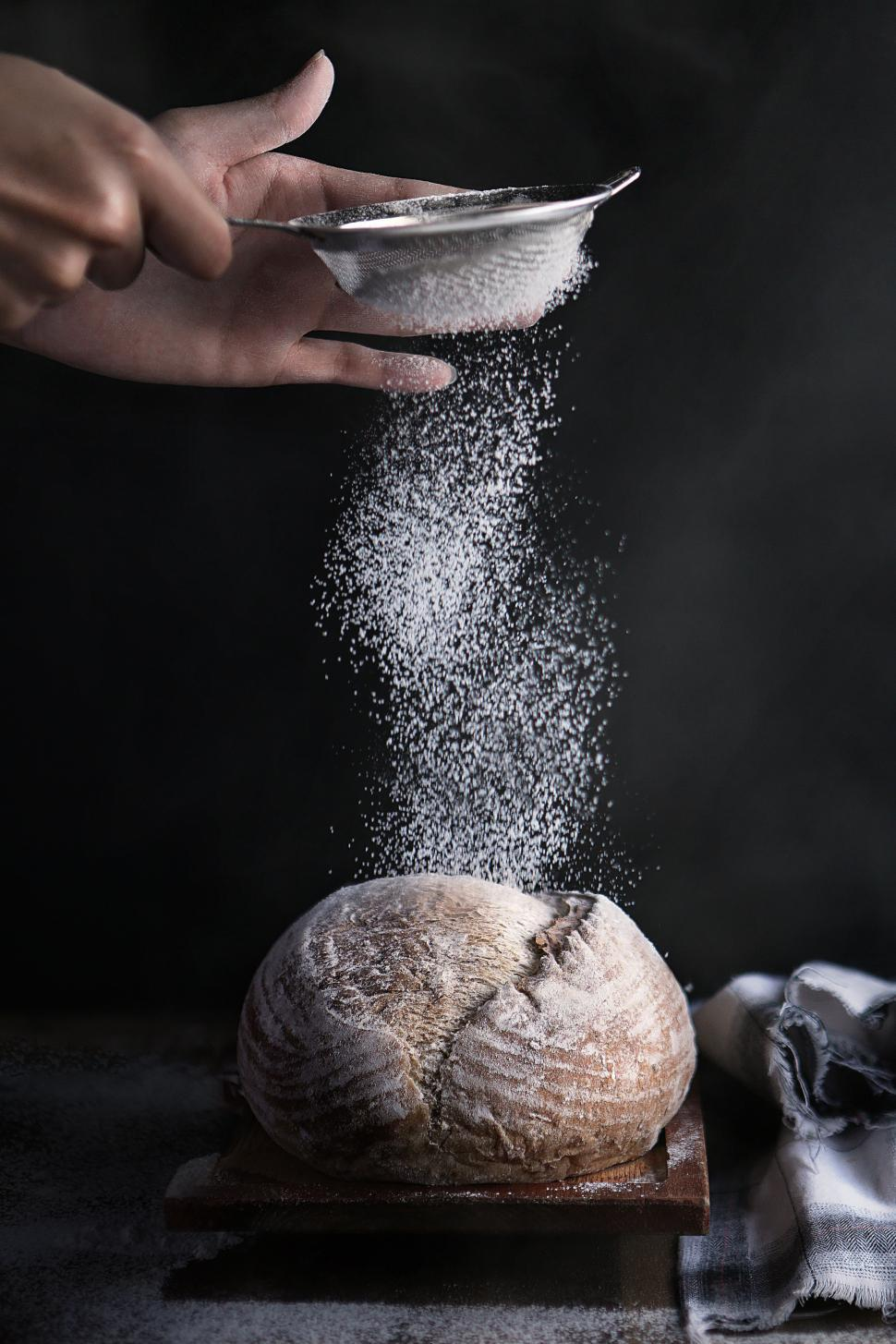 Download Free Stock HD Photo of Baker sprinkles powdered flour on bread Online