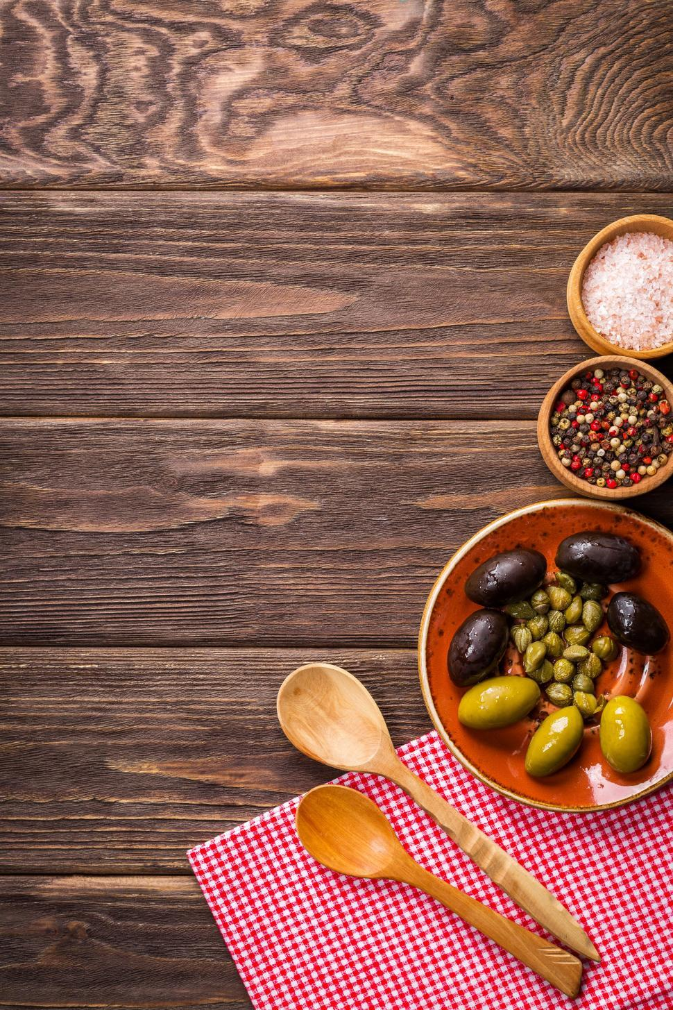 Download Free Stock HD Photo of Overhead view of olives and garlic in a plate on the wooden table Online