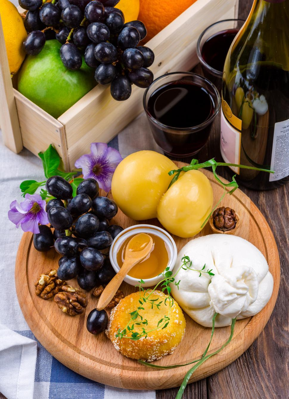 Download Free Stock Photo of Cheese Plate with black grapes on wooden board