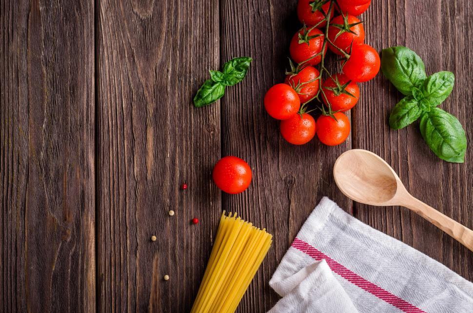 Download Free Stock Photo of Overhead view of a bundle of raw spaghetti and fresh tomatoes