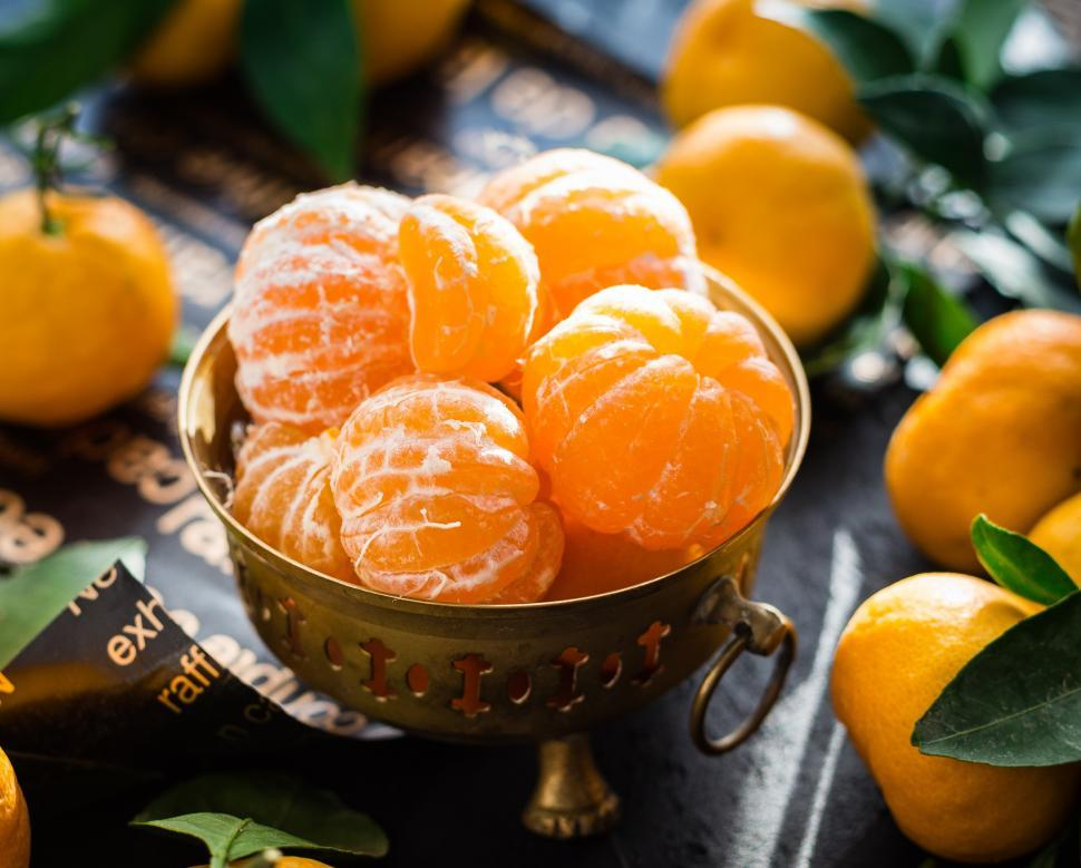 Download Free Stock HD Photo of Close up of peeled mandarins in a brass fruit bowl Online