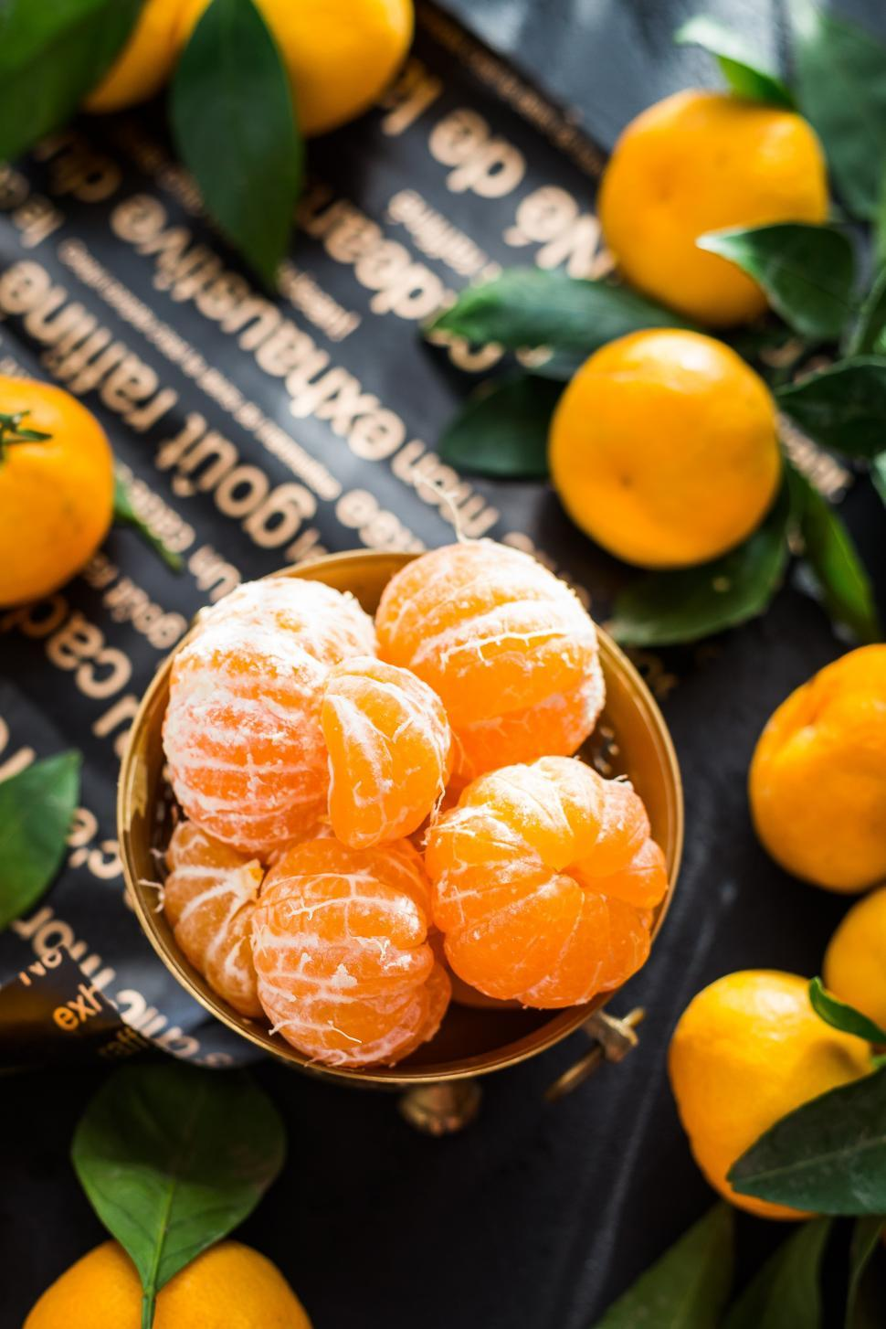 Download Free Stock Photo of overhead view of peeled mandarins in a brass fruit bowl