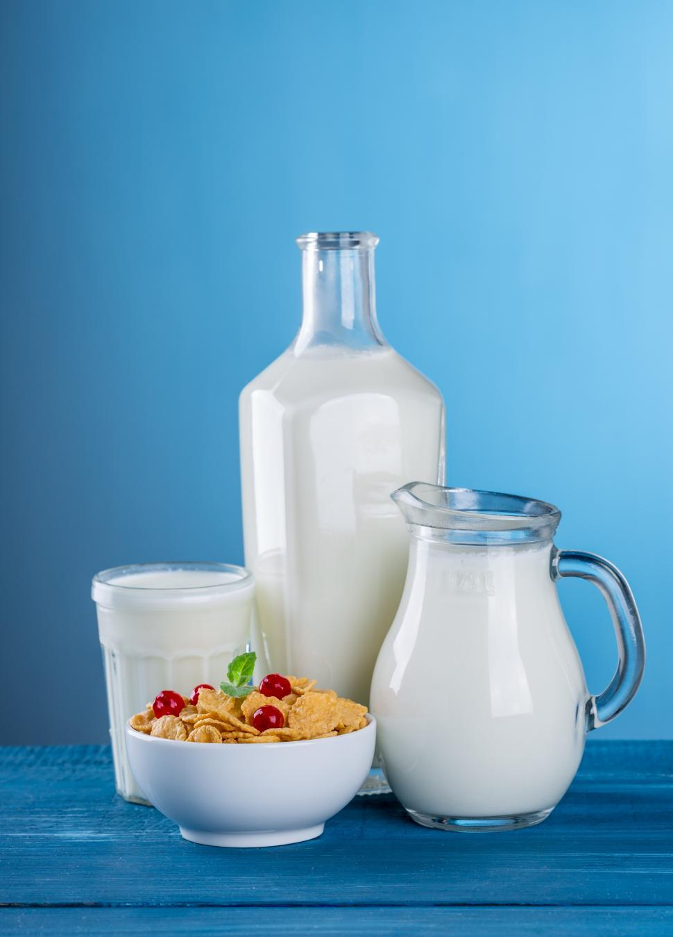 Download Free Stock HD Photo of Close up of a glass, a pitcher and a bottle containing milk Online