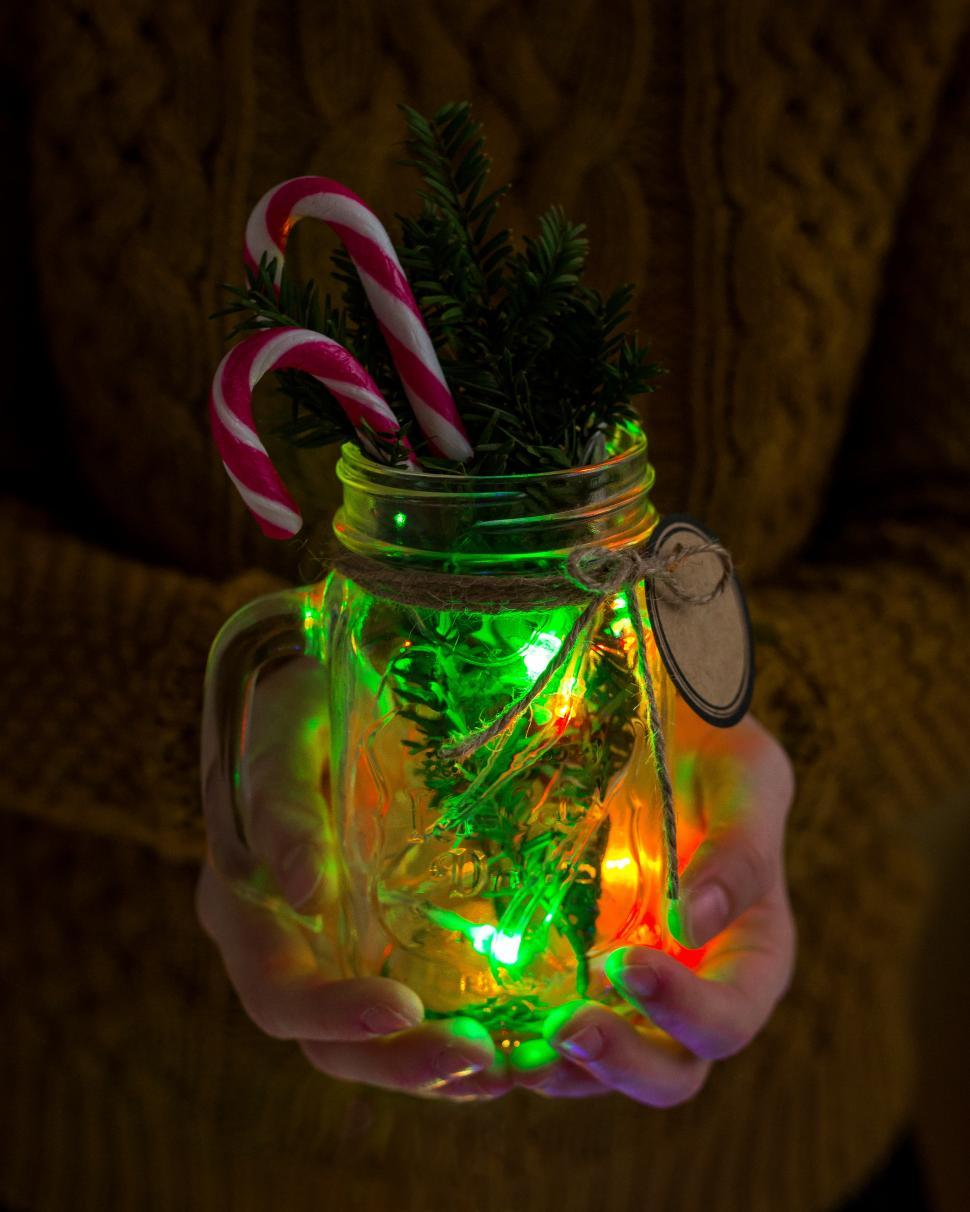 Download Free Stock HD Photo of Close up of hands holding a mason jar with Christmas decorations Online
