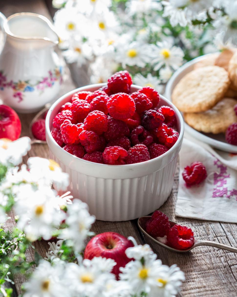 Download Free Stock HD Photo of Table with flowers and a bowl of raspberries Online