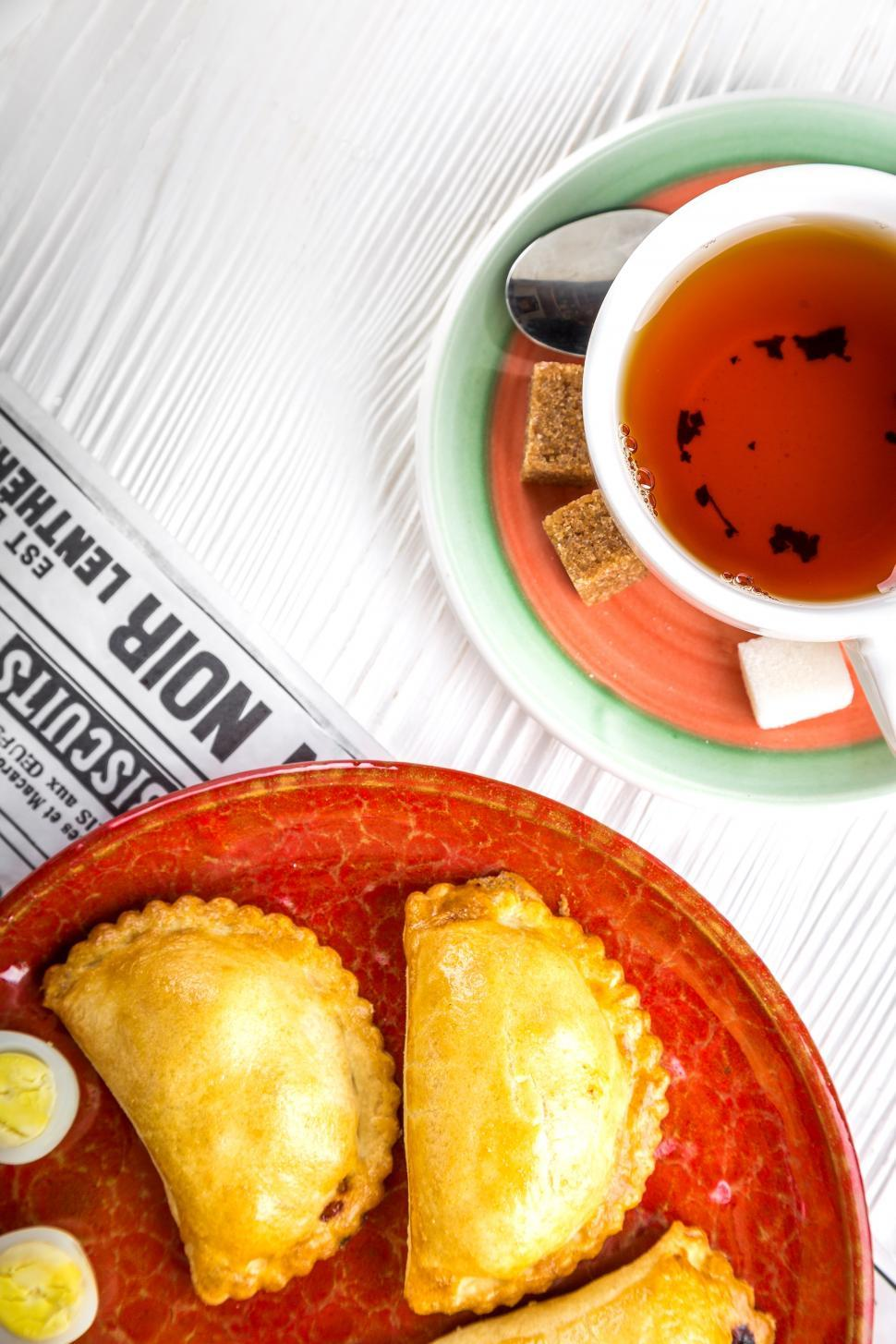 Download Free Stock HD Photo of Over head view of a cup of tea and Russian pirozhki baked patties Online