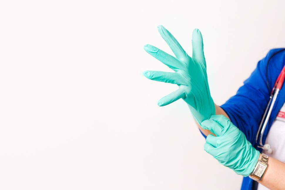 Download Free Stock Photo of Provider pulling on gloves, with white copyspace