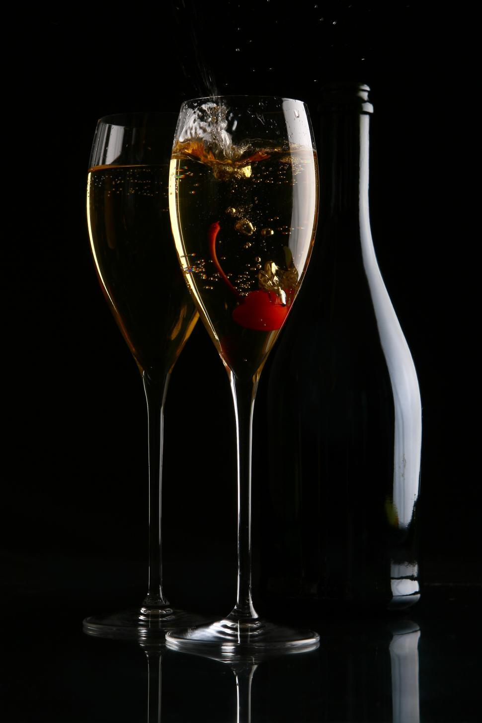 Download Free Stock HD Photo of two elegant glasses with gold champagne and cherry Online