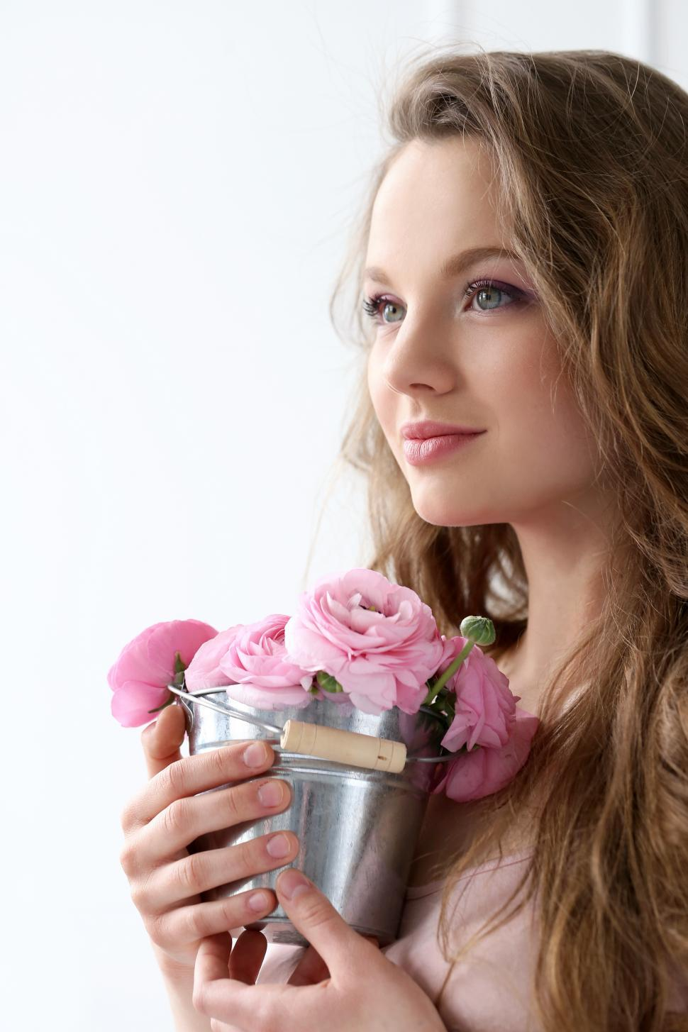 Download Free Stock Photo of Beautiful girl holding decorative bucket of flowers