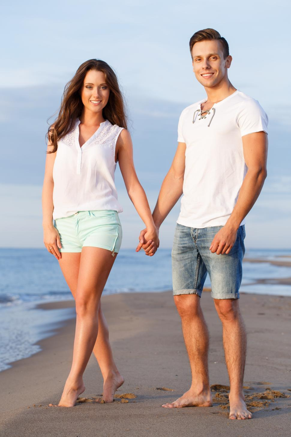 Download Free Stock Photo of Beautiful couple holding hands on the beach