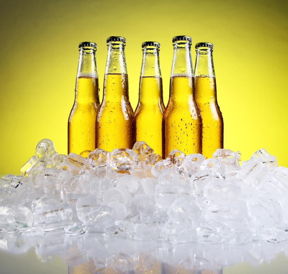 Download Free Stock HD Photo of Cold bottles of beer in ice on yellow background Online