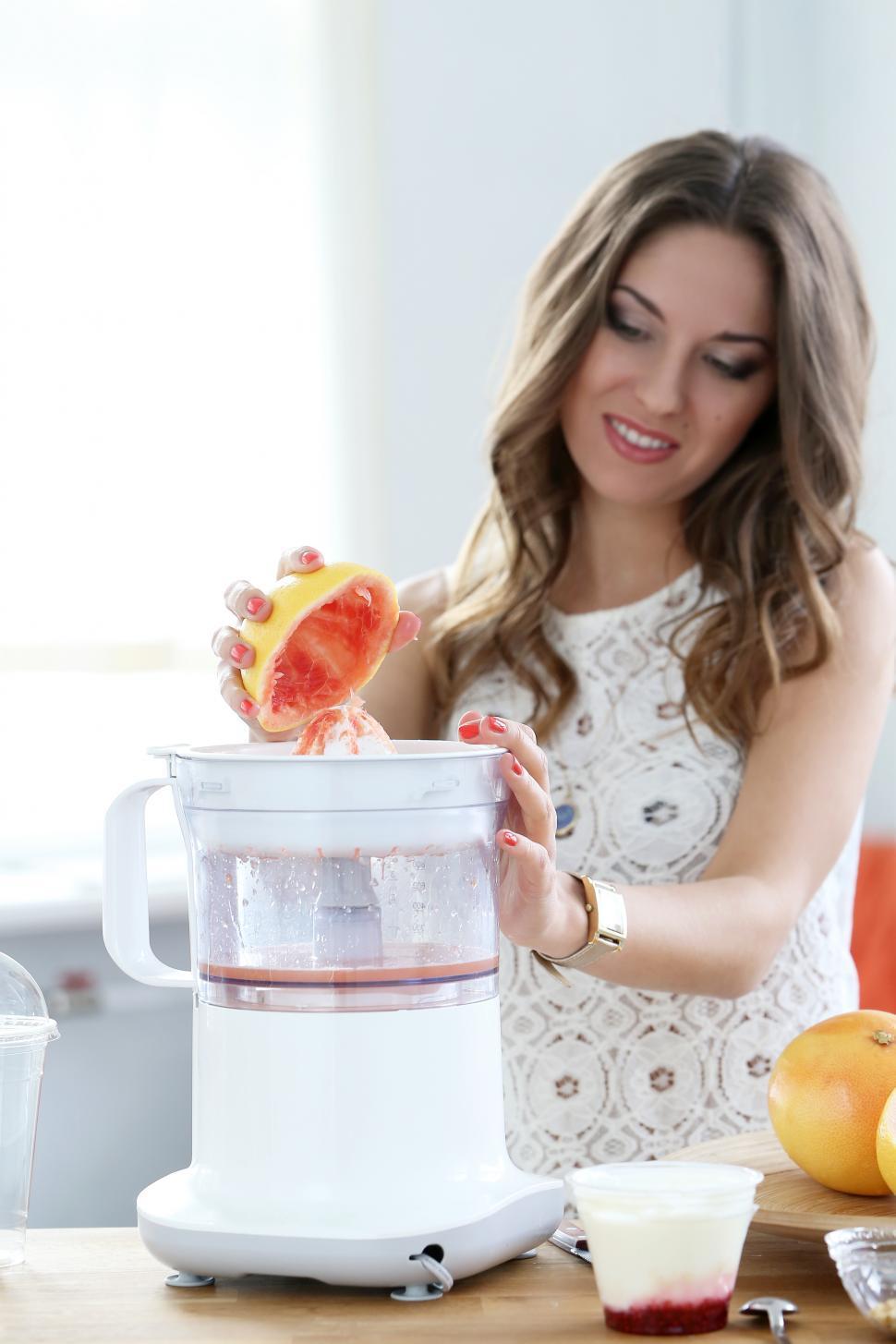 Download Free Stock HD Photo of Beautiful woman making orange juice Online