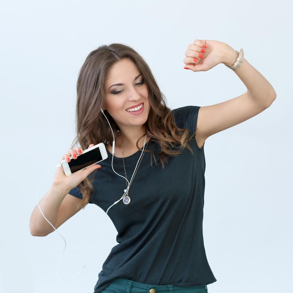 Download Free Stock HD Photo of Woman dancing to music from mobile phone Online