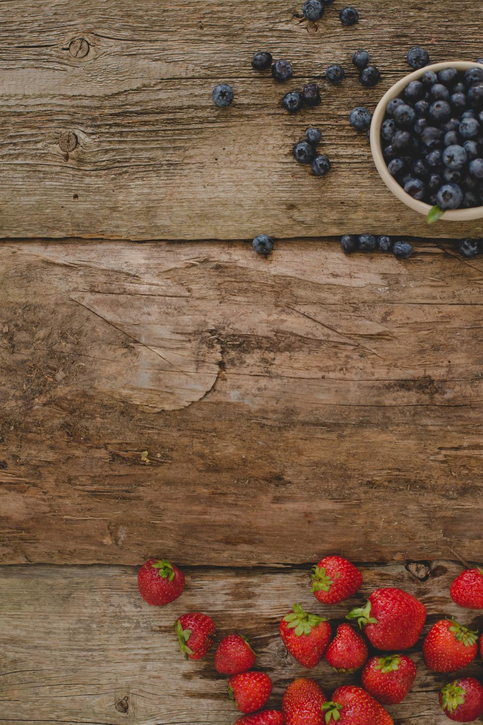 Download Free Stock HD Photo of Berries on the wooden table with copyspace Online
