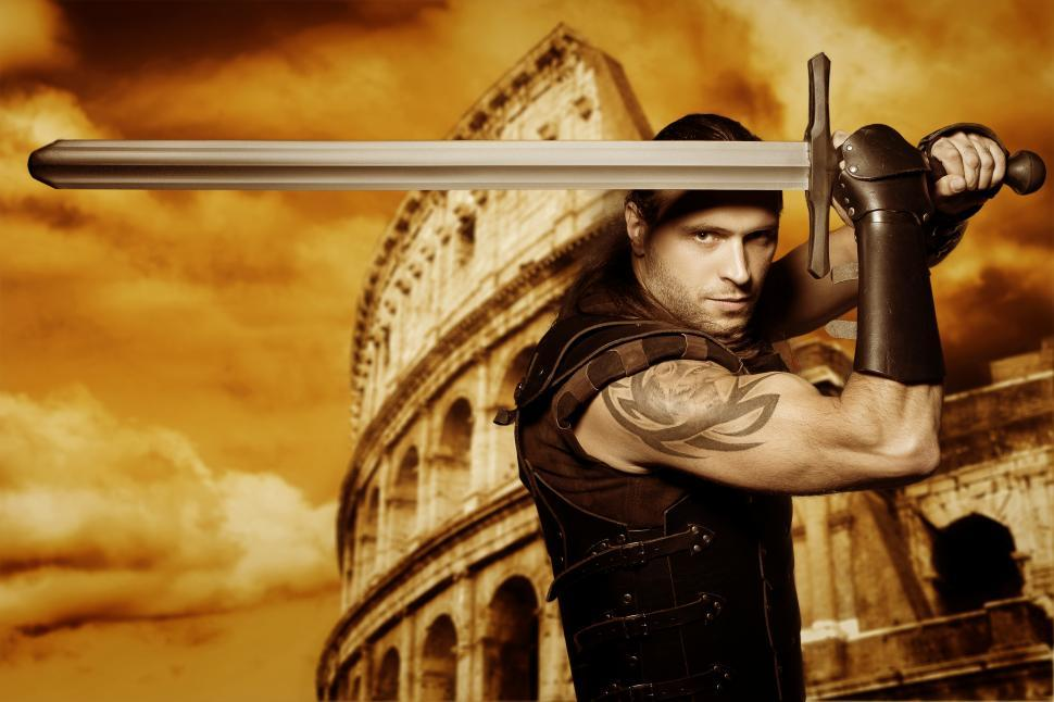 Download Free Stock Photo of Lone gladiator with a longsword stands in front of Colosseum