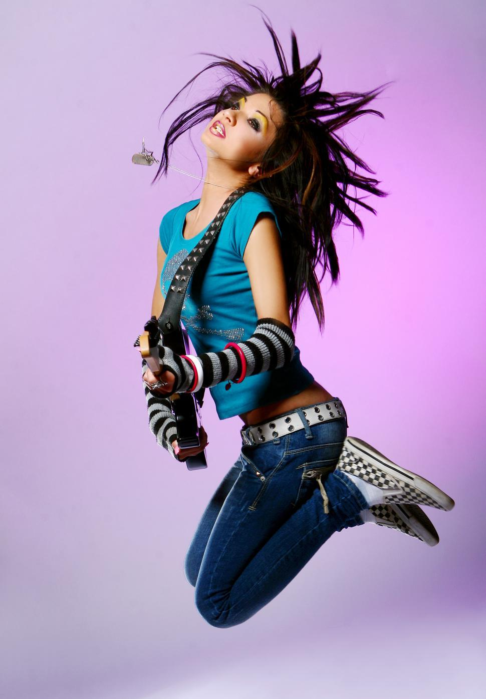 Download Free Stock HD Photo of young musician jumps with guitar Online