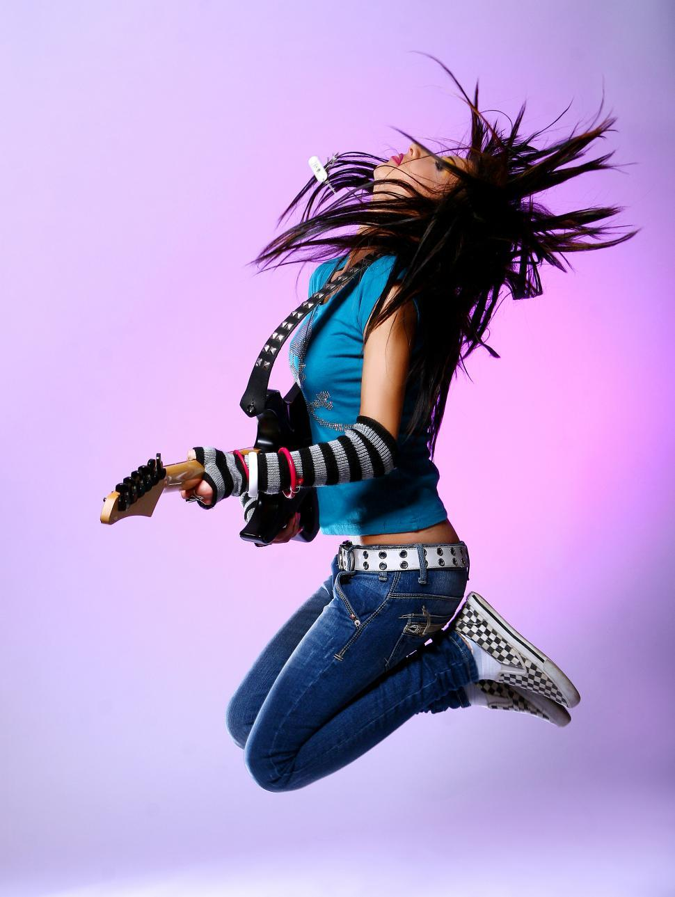 Download Free Stock Photo of woman jumping in air with guitar