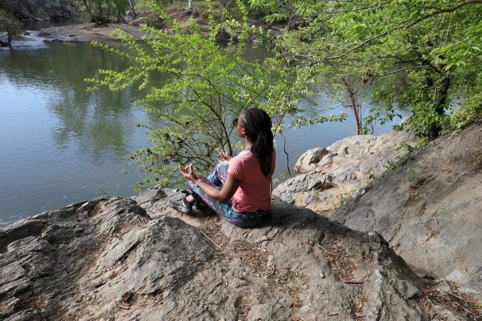 Download Free Stock Photo of Young Woman sitting in lotus yoga pose near lake