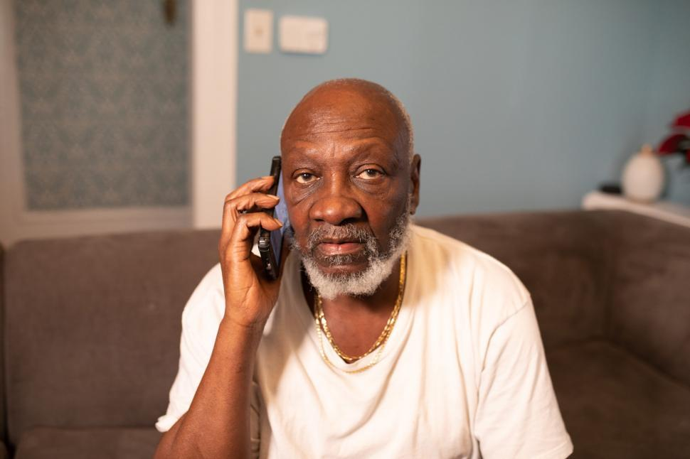 Download Free Stock Photo of Older Man talking on smartphone at home - looking at camera