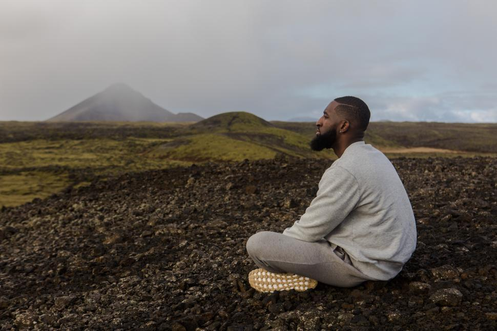 Download Free Stock Photo of Young Man in Grey Sweatshirt Sitting Alone Near Mountains