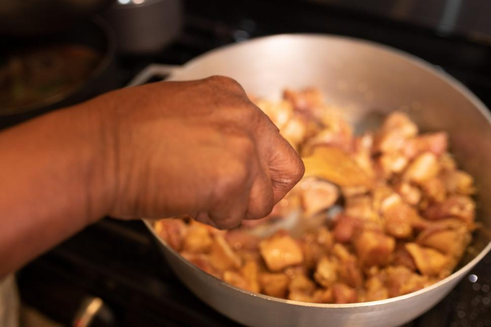 Download Free Stock Photo of Hand with meat pieces in cooking pot