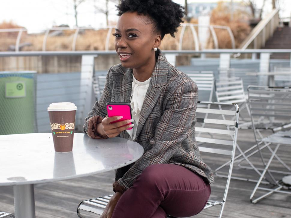 Download Free Stock Photo of Young business woman in tweed blazer holding iPhone - looking at camera