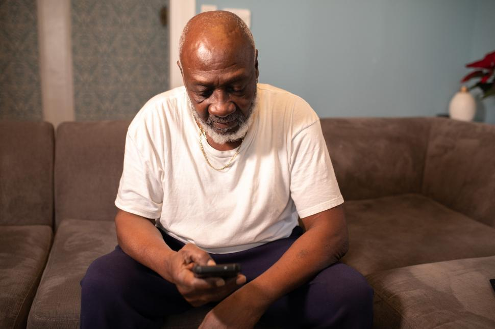 Download Free Stock Photo of Older Man in white shirt holding smartphone at home