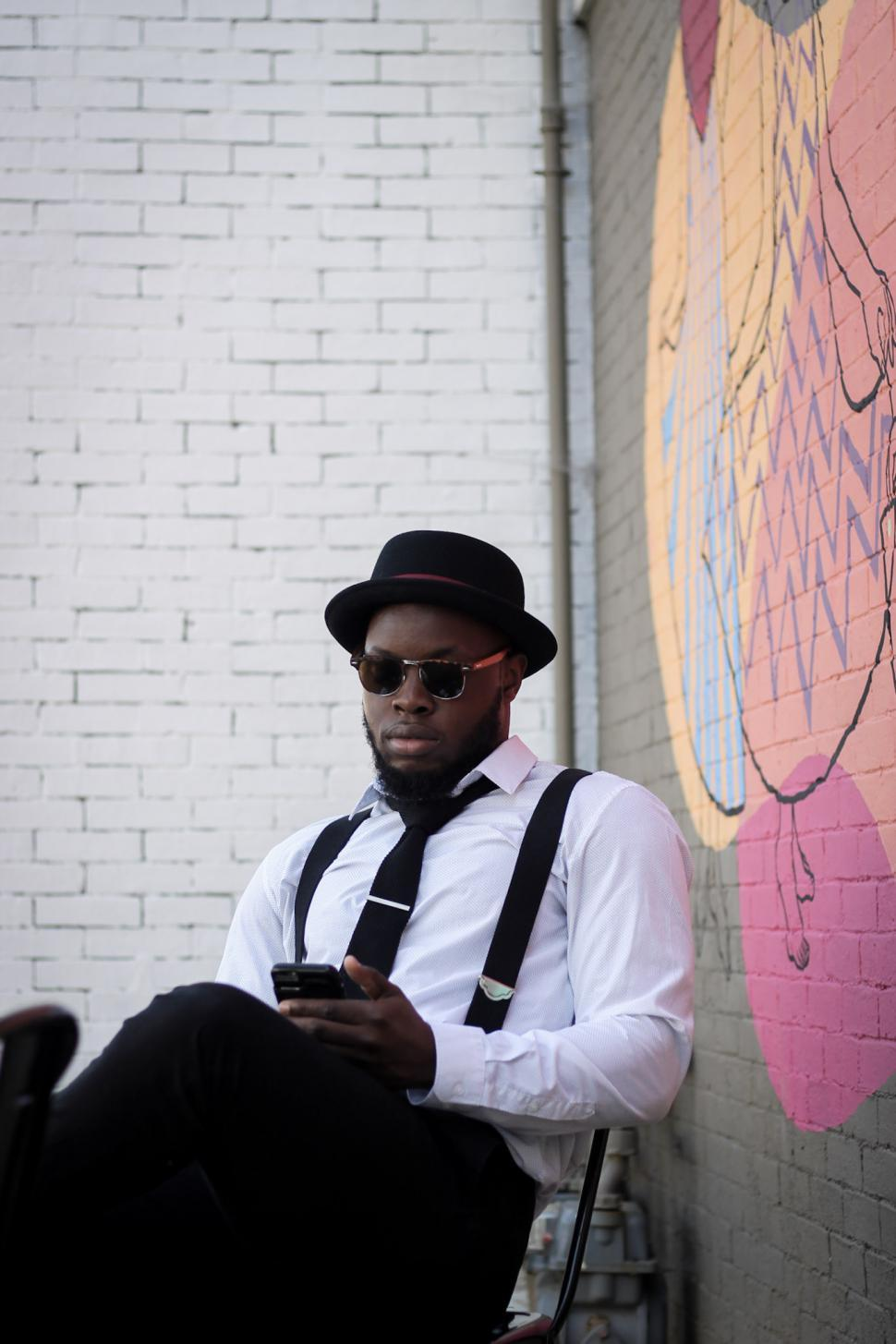 Download Free Stock Photo of Young Man wearing suspenders and hat using cell phone against graffiti wall