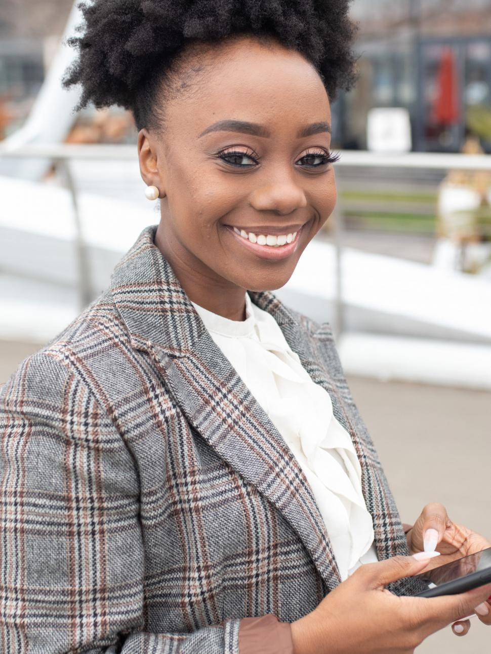 Download Free Stock Photo of Young smiling business woman in tweed blazer, with smartphone