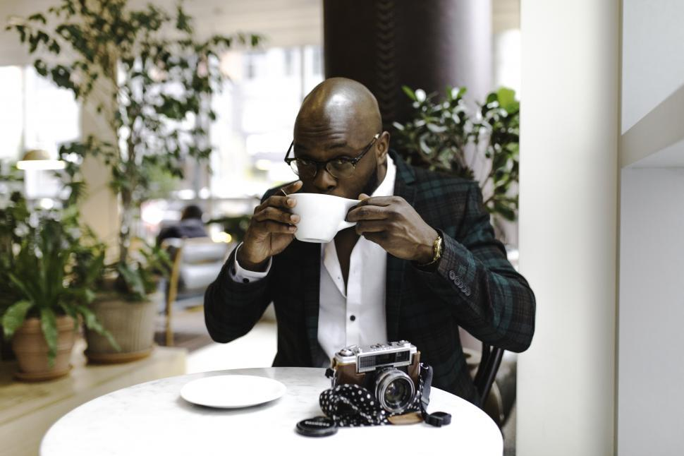 Download Free Stock Photo of Young well-dressed man in spectacles holding a coffee cup with camera