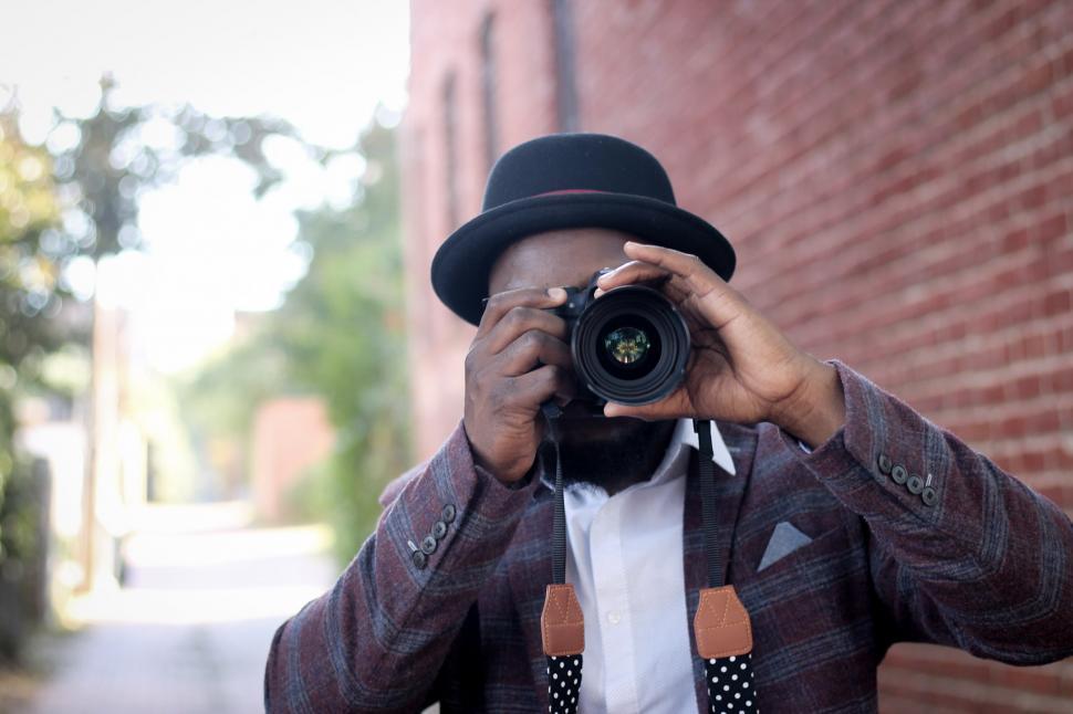 Download Free Stock Photo of Man wearing black hat holding professional camera