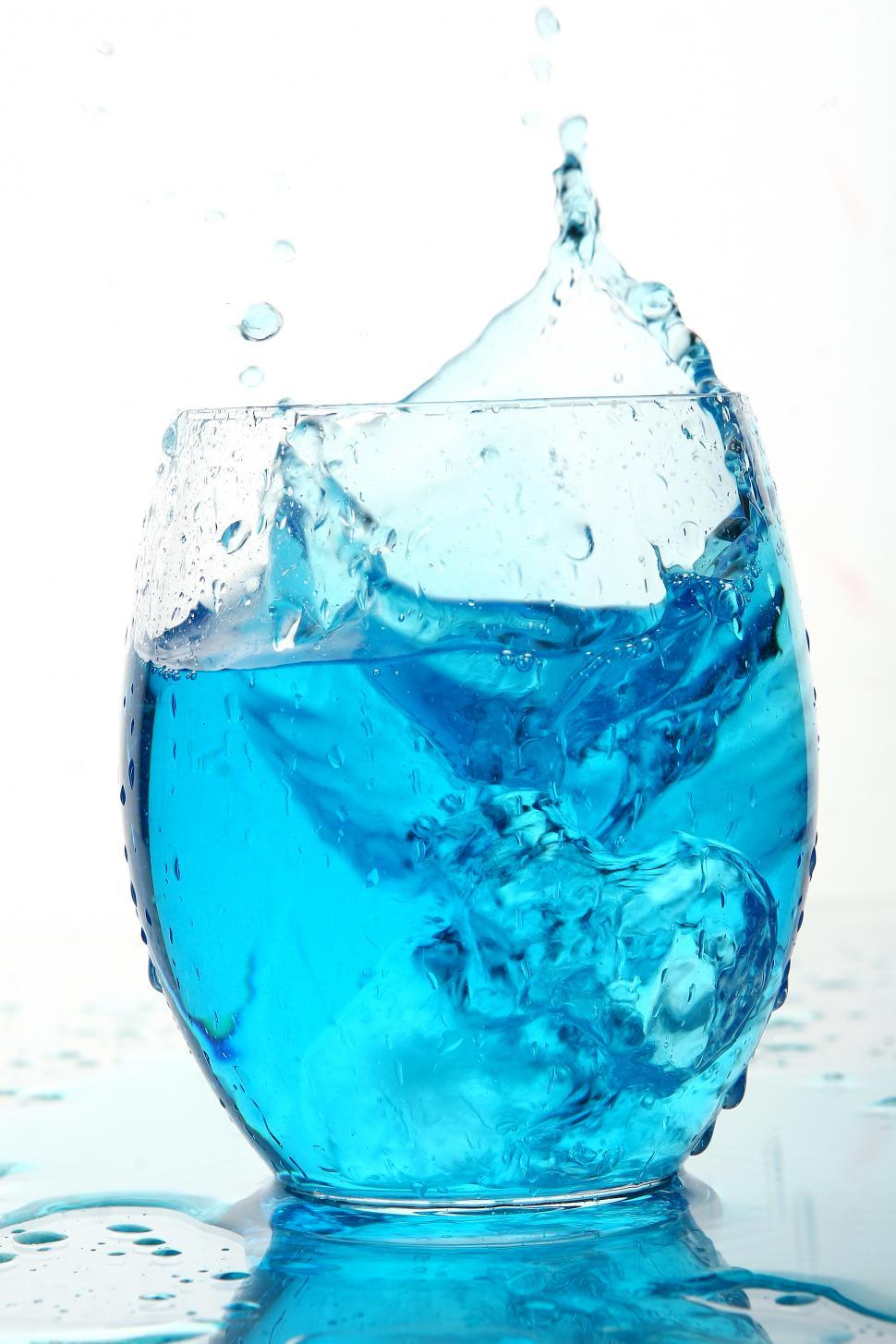 Download Free Stock Photo of Ice splashes into blue beverage