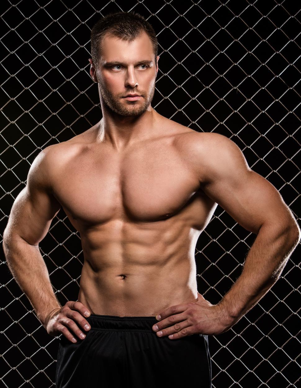 Download Free Stock Photo of Shirtless muscular man standing with hands on hips