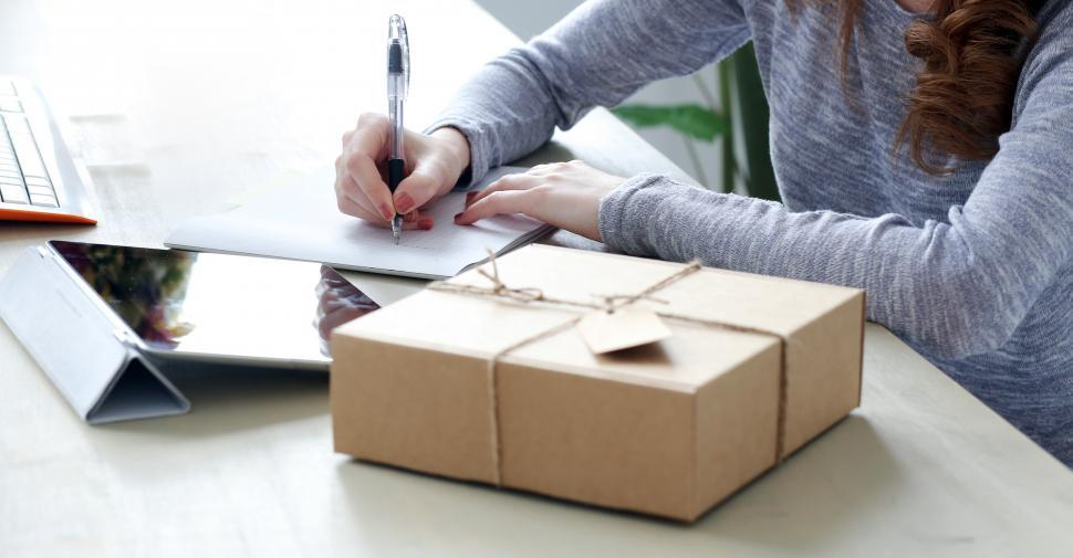 Download Free Stock Photo of Package on the desk, woman writing on the card