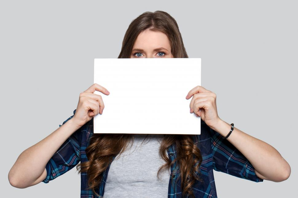 Download Free Stock Photo of Young woman peeking over blank white card