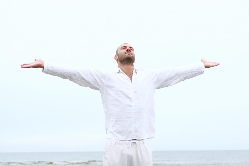 Download Free Stock Photo of Man on the beach with arms spread