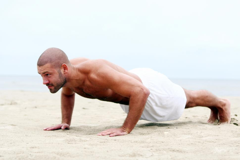 Download Free Stock Photo of Fit man doing pushups on the beach