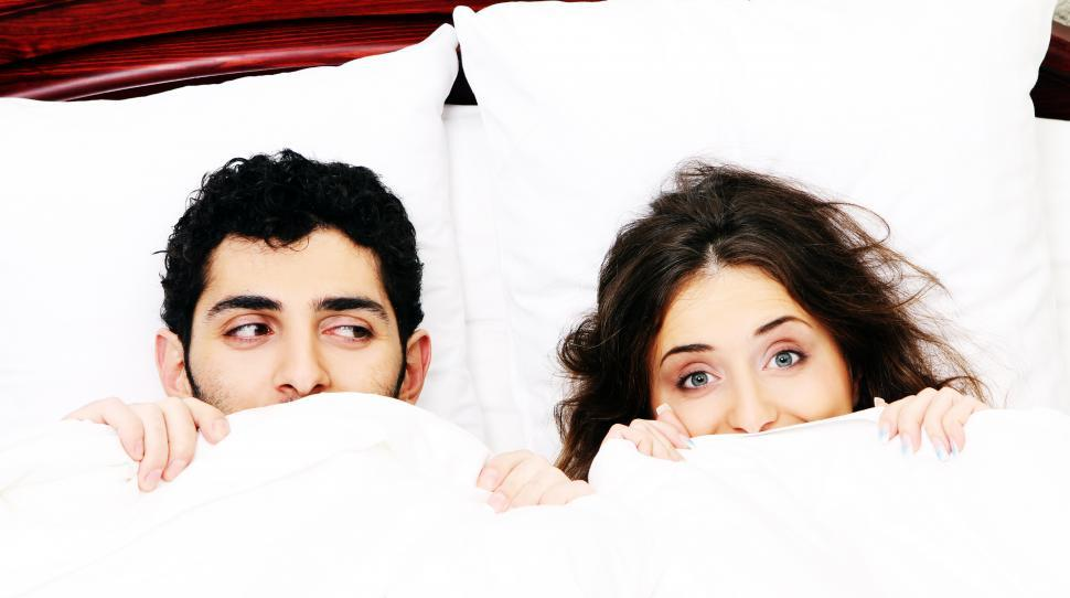 Download Free Stock Photo of Young couple in bed with covers pulled up
