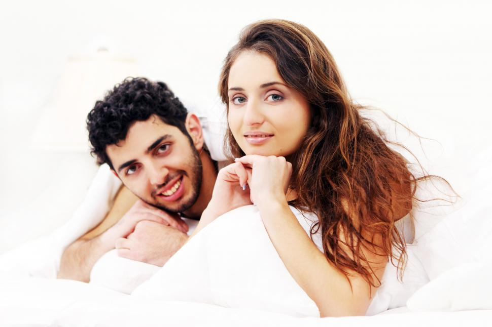 Download Free Stock Photo of Young couple sitting up in bed
