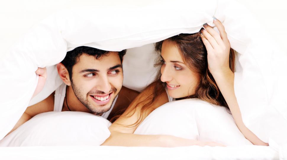 Download Free Stock Photo of Young couple under the covers together